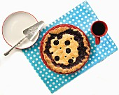 Blueberry pie from above on polka dot placemat with coffee