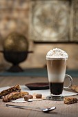 Espresso cocktail layered in tall glass with whipped cream nutmeg and biscotti