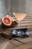 Champagne cocktail in Martini glass with ruby red pink grapefruit