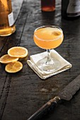 A champagne cocktail with orange garnish