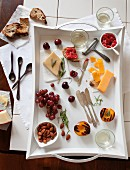 Assortment of Cheeses and Summer Fruits on White Tray. From Above