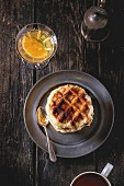 Metal plate with homemade belgian waffles with orange syrup in vase and vintage cup of tea over old wooden table