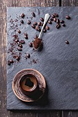 Brown ceramic cup of fresh coffee, tea spoon with ground coffee and coffee beans over black slate as background