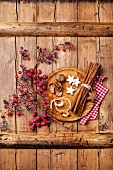 Xmas cookies, walnuts, dried orange peel, cinnamon sticks and branch with red berries on wooden texture background