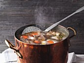 A copper pot with homemade, steaming meat stock
