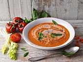 Creamy tomato soup with celery, cream and fresh basil