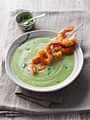 Pea and avocado soup with grilled prawn skewer