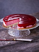 Cranberry and fresh cheese tart, sliced on a cake stand