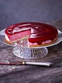 Cranberry-Frischkäsetorte, angeschnitten auf Kuchenständer