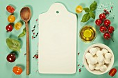 White ceramic serving board and caprese salad ingredients over light blue background