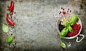 Chilischoten, Basilikum und bunte Pfefferkörner in einer Schüssel auf rustikalem Untergrund