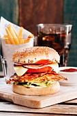 Chicken burger with bacon and glass of cola