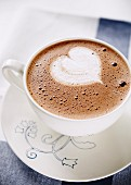 Cup of hot chocolate with whipped cream shaped heart