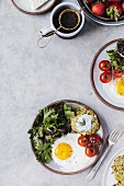 A fried egg, lettuce and courgette fritters and tomatoes served on plates