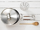 Kitchen utensils: cooking pot, measuring cup, spoon and fork