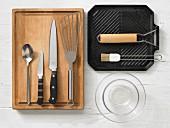 Verschiedene Küchenutensilien: Grillpfanne, Glasschalen, Pfannenwender, Messer, Löffel