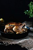 Roasted lemon chicken with a crisp skin displayed in a cast iron skillet right after it came out of the oven