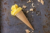 Homemade mango ice cream in waffle cone with wafer crumb over rusty metal textured background