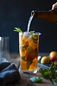 Fruchtcocktail mit Pflaumen, Orangen und Basilikuml wird zubereitet
