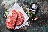 Raw fresh marbled meat Black Angus Steak Ribeye and seasonings on metal background