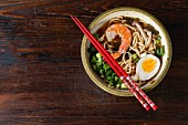 Ceramic bowl of asian ramen soup with shrimp, noodles, spring onion, sliced egg and mushrooms