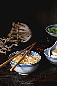 Chinese porcelain bowl of asian ramen soup with feta cheese, noodles, spring onion and mushrooms