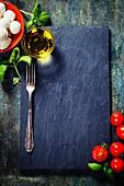 Schieferplatte umrahmt von Kirschtomaten, Basilikum, Mozzarella und Olivenöl für Caprese-Salat