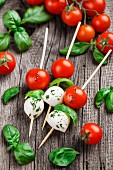 Skewers with tomato, basil and mozarella on a rustic background