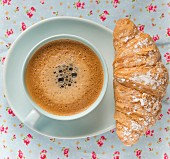 Frothy coffee in a blue cup and saucer on a floral table cloth, with croissant pastry