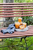 Apricot chutney jars on vintage tray with grey kitchen towel on garden bench