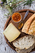 Cheese platter, rustic bread and chutney on wooden board on white wooden table