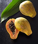 Two papayas, one halved, with a palm leaf