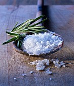 Sea salt flakes and rosemary on an old wooden spoon
