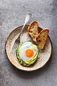 Breakfast with baked egg in zucchini noodles nest with bread toast on a ceramic plate