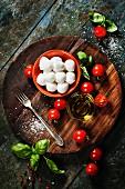Kirschtomaten, Basilikum, Mozzarella und Olivenöl für Caprese-Salat