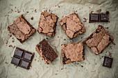Schokoladen-Brownies und Schokoladenstücke auf Backpapier (Aufsicht)