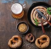 Bratwurstschnecke in der Pfanne dazu Bier, Senf und Brezen