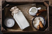 Ingredients for making rice pudding: Bowl of white uncooked rice, sugar, cinnamon sticks, milk and cream in wood box