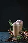 Two glasses of cafe latte with pink marshmallow with Christmas decor, candies, spices, coffee beans and fir tree