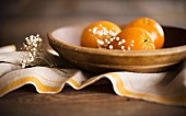 Three ripe oranges in a rustic wooden bowl with linen and flowers