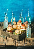 Different burgers with sticks in wooden tray and lemonade in bottles with straws on rustic shabby table
