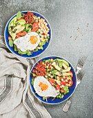 Healthy breakfast bowls with fried egg, chickpea sprouts, seeds, vegetables and greens over grey concrete background