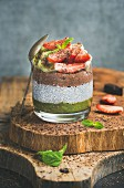 Matcha, almond milk, cocoa chia seed pudding with fresh fruit, berries, mint, chocolate in glass