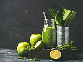 Green smoothie in bottle with apple, romaine lettuce, lime and mint on dark background