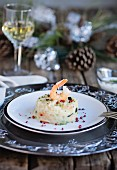 Shrimps and zucchini risotto on wooden table with christmas decorations