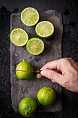 Hand cutting limes with a vintage knife on slate board