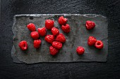 Wet raspberries on black slate board