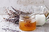 Open glass jar of liquid honey with honeycomb and silver spoon inside, glass jug of milk and bunch of dry lavender