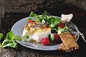 Melting sliced grilled goat cheese, served with liquid honey, lavender, raspberries, wholegrain toast and green salad