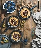 Pflaumen-Crostata mit Walnüssen in gusseisernen Pfännchen auf rustikalem Holztisch